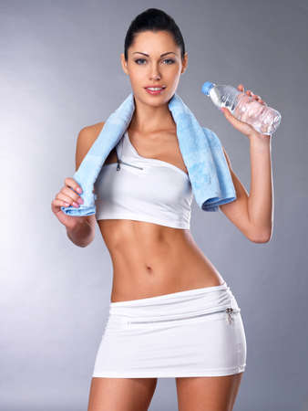 Portrait of a healthy woman with  bottle of water and towel.  Healthy  lifestyle concept. Sporty girl with beautiful body photo