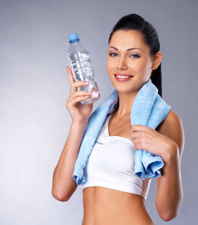 Smiling healthy woman with  bottle of water and towel.  Healthy  lifestyle concept. photo