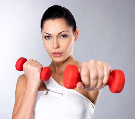 beautiful young woman with dumbbells -  grey studio background. Healthy lifestyle concept. Stock Photo - 16300966