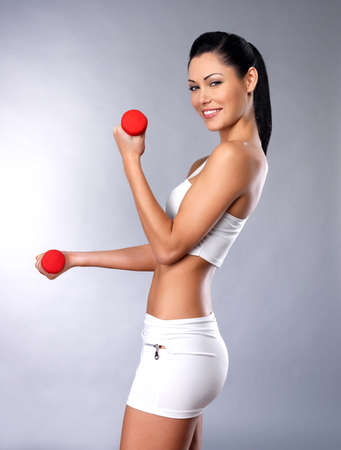 beautiful happy woman with dumbbells -  grey studio background. Healthy lifestyle concept. photo