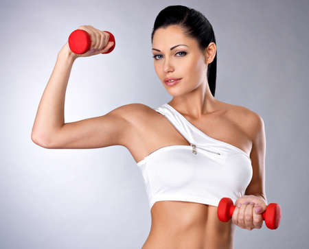 barbell: Portrait of beautiful young woman with dumbbells -  grey studio background. Healthy lifestyle concept. Stock Photo