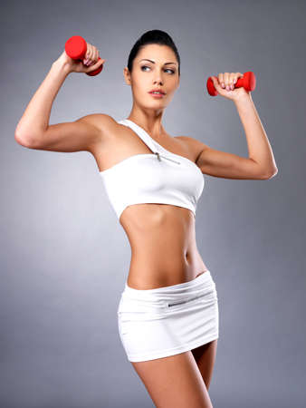 sport girl: beautiful young woman with dumbbells -  grey studio background. Healthy lifestyle concept.