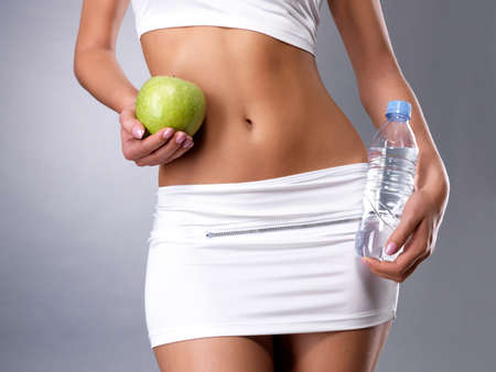Healthy female body with apple and bottle of water. Healthy fitness and eating lifestyle concept.