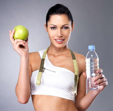 Portrait of a healthy woman with apple and bottle of water. Healthy fitness and eating lifestyle concept. Stock Photo - 16300969