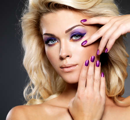 Beautiful blond woman with beauty purple manicure and makeup of eyes  Fashion model with curly hairstyle  photo