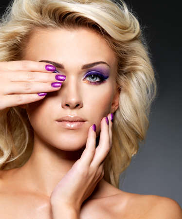 Beautiful blond woman with beauty purple manicure and makeup of eyes  Fashion model with curly hairstyle  Stock Photo - 16317296