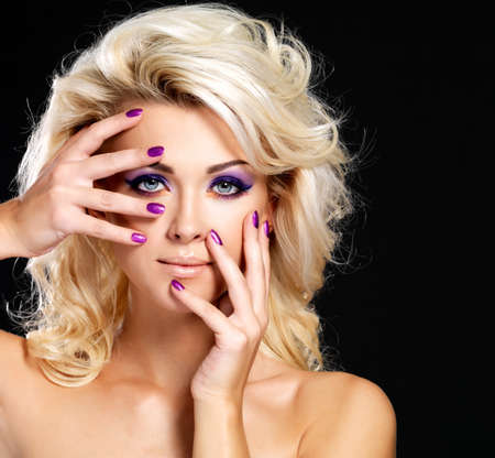 Beautiful blond woman with beauty purple manicure and makeup of eyes  Fashion model with curly hairstyle  Stock Photo - 16317289