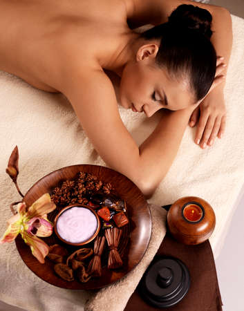 candles spa: Calm woman after massage relaxing in spa salon. Beauty treatment concept.