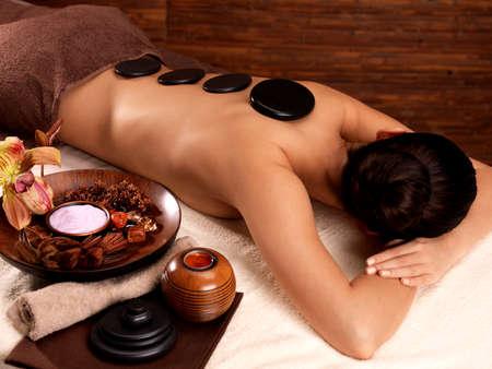 main sur l epaule: Jeune femme ayant massage aux pierres dans le salon de spa. Mode de vie sain. Banque d'images