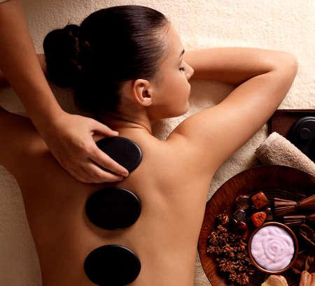 masajes relajacion: Mujer joven que consigue masaje con piedras calientes en el sal�n de spa. Belleza concepto de tratamiento.
