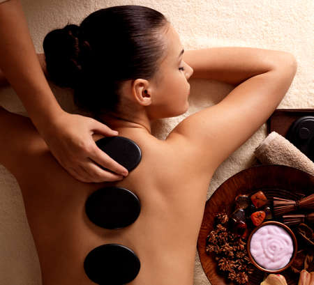 spa therapy: Young woman getting hot stone massage in spa salon. Beauty treatment concept.