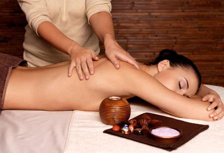 masoterapia: Masajista haciendo masaje en el cuerpo de la mujer en el salón de spa. Belleza concepto de tratamiento.