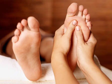 massaging: Massage of human foot in spa salon - Soft focus image