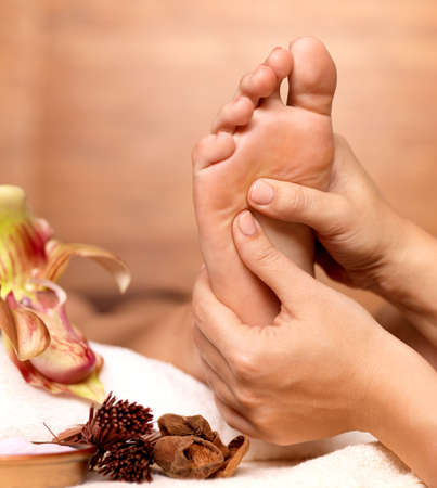 hands massage: Massage of human foot in spa salon - Soft focus image