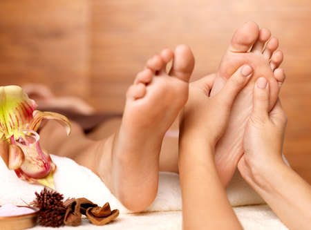 human foot: Massage of human foot in spa salon - Soft focus image