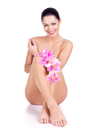 erotic girl: Beautiful smiling nude woman with flowers in hands sits on the white background