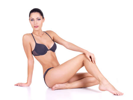 Woman with beautiful long slim legs in bikini sits  on white background photo