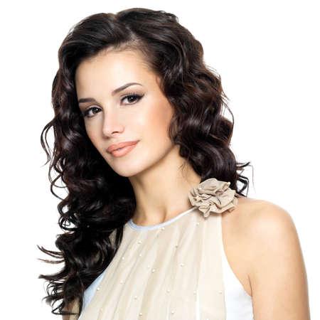 cabello rizado: una mujer joven con el pelo largo rizado belleza. Moda modelo posando en el estudio. Foto de archivo