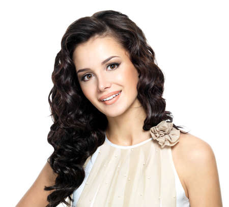hair curly: una mujer joven con el pelo largo rizado belleza. Moda modelo posando en el estudio. Foto de archivo