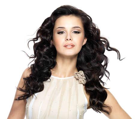 아름다움 긴 곱슬 머리를 가진 아름 다운 갈색 머리 여자. 물결 모양의 헤어 스타일과 패션 모델