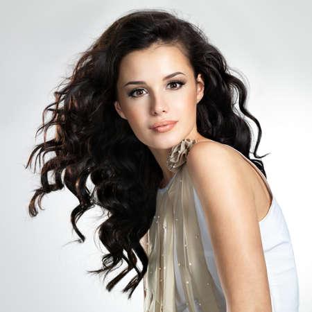 dishevel: Bella giovane donna con lunghi capelli castani. Modello piuttosto pone in studio.