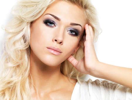 Belle femme blonde aux longs cheveux boucl�s et le maquillage style. Fille posant sur fond blanc photo