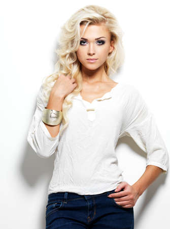 Fashion model posing in studio. Portrait of a beautiful blond woman with saturated makeup. Girl posing on white background photo