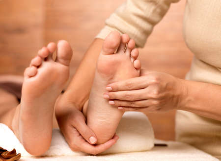 body massage: Massage of human foot in spa salon - Soft focus image