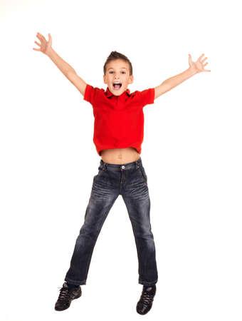 niño saltando: Retrato de muchacho riendo feliz saltando con las manos levantadas hacia arriba - aislados en fondo blanco