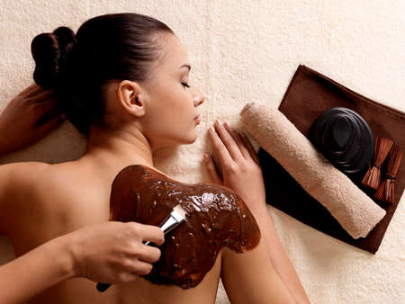 body spa: Spa therapy for young woman receiving cosmetic mask on back at beauty salon Stock Photo