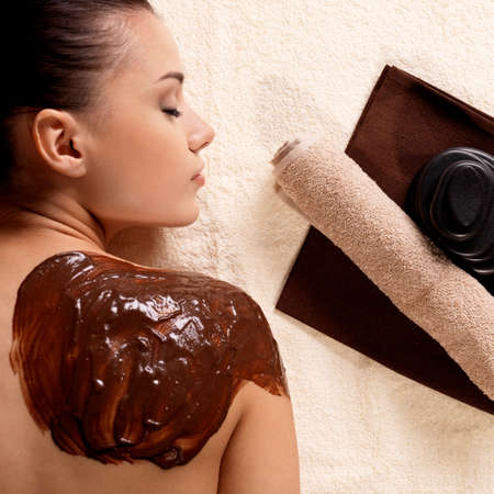 body massage: Spa therapy for young woman receiving cosmetic mask on back at beauty salon Stock Photo