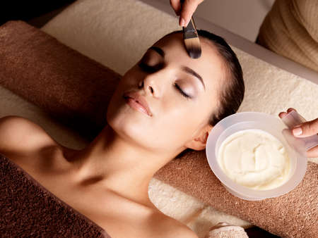 spa treatment: Spa therapy for young woman receiving facial mask at beauty salon - indoors