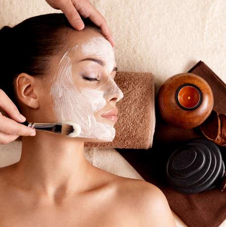 facial massage: Cure thermale pour jeune femme recevant le masque facial au salon de beaut� - � l'int�rieur Banque d'images