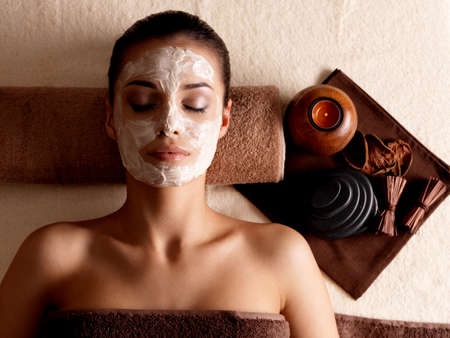 Young woman relaxing with facial mask on face at beauty salon- indoors photo