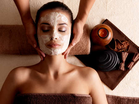 masajes faciales: Spa masaje para la mujer joven con la máscara facial en el rostro - en el interior