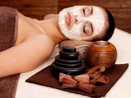 tratamiento facial: Joven mujer de relax con la máscara cosmética en la cara de la belleza del salón-en interiores