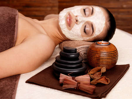 beauty mask: Young woman relaxing with cosmetic mask on face at beauty salon- indoors