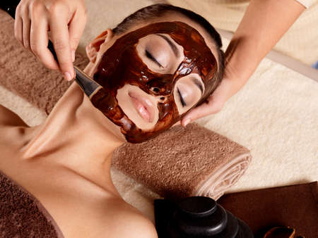 Spa therapy for young woman receiving facial mask at beauty salon - indoors photo