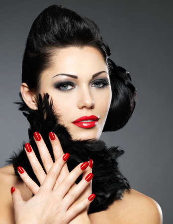 finger nail: Beautiful fashion woman with red nails, creative hairstyle and makeup - Model posing in studio