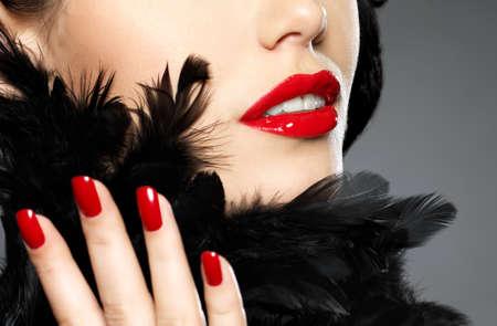 labbra sensuali: Macro fotografia di moda donna con unghie rosse e labbra sensuali