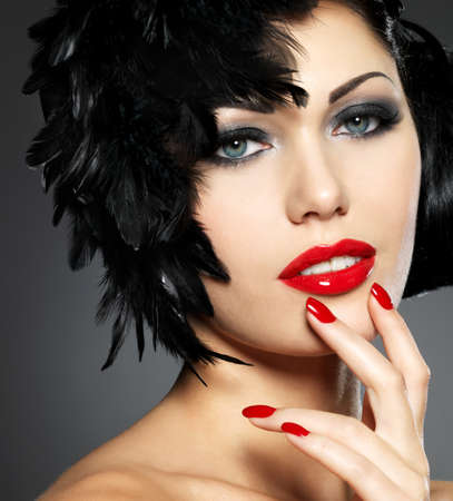 finger to lips: Beautiful fashion woman with red nails, creative hairstyle and makeup - Model posing in studio