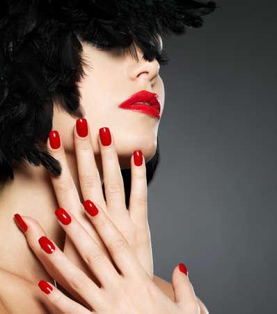 manicura: Macro foto de la mujer con las u�as rojas de la moda y los labios sensuales Foto de archivo
