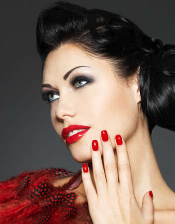 red nails: Beautiful fashion woman with red nails, creative hairstyle and makeup - Model posing in studio