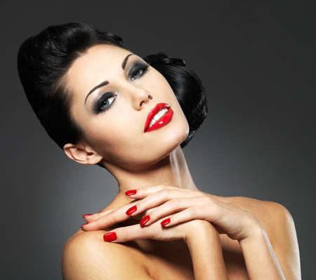 high fashion model: Beautiful fashion woman with red nails, creative hairstyle and makeup - Model posing in studio