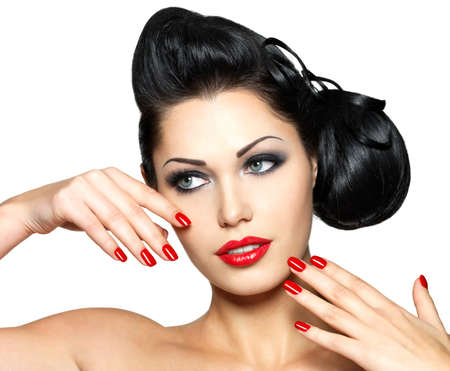 Beautiful fashion woman with red lips, nails and creative hairstyle - isolated on white background Stock Photo - 16690769