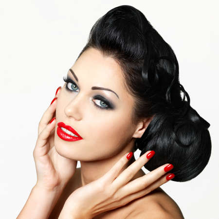 Beautiful fashion woman with red lips, nails and creative hairstyle - isolated on white background Stock Photo - 16690764