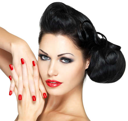 red nails: Beautiful fashion woman with red lips, nails and creative hairstyle - isolated on white background