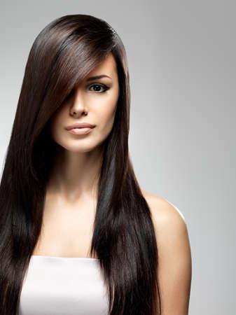hosszú haj: Gyönyörű nő, hosszú, egyenes haj. Divatmodell pózol a stúdióban.