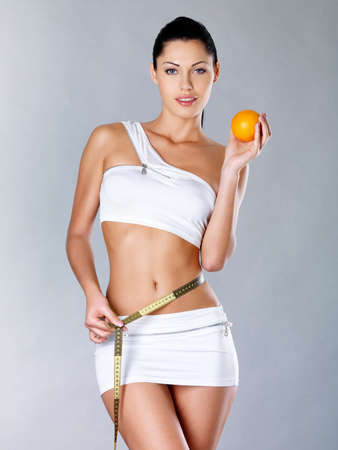 Healthy woman with a measuring tape and holding the orange. Healthy lifestyle cocnept. photo