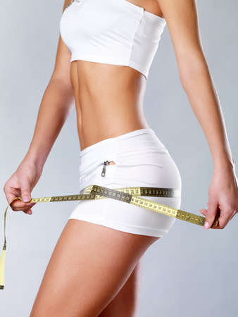measurement tape: Beautiful feamle body with measuring tape. Healthy lifestyle cocnept. Stock Photo
